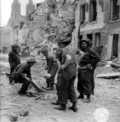 Des sapeurs du génie canadien rebouchent un trou de bombe, dans le bas de la rue de Bayeux à Caen. En arrière-plan l'Abbaye-aux-Hommes (Saint-Etienne) à conservé ses deux clochers intacts