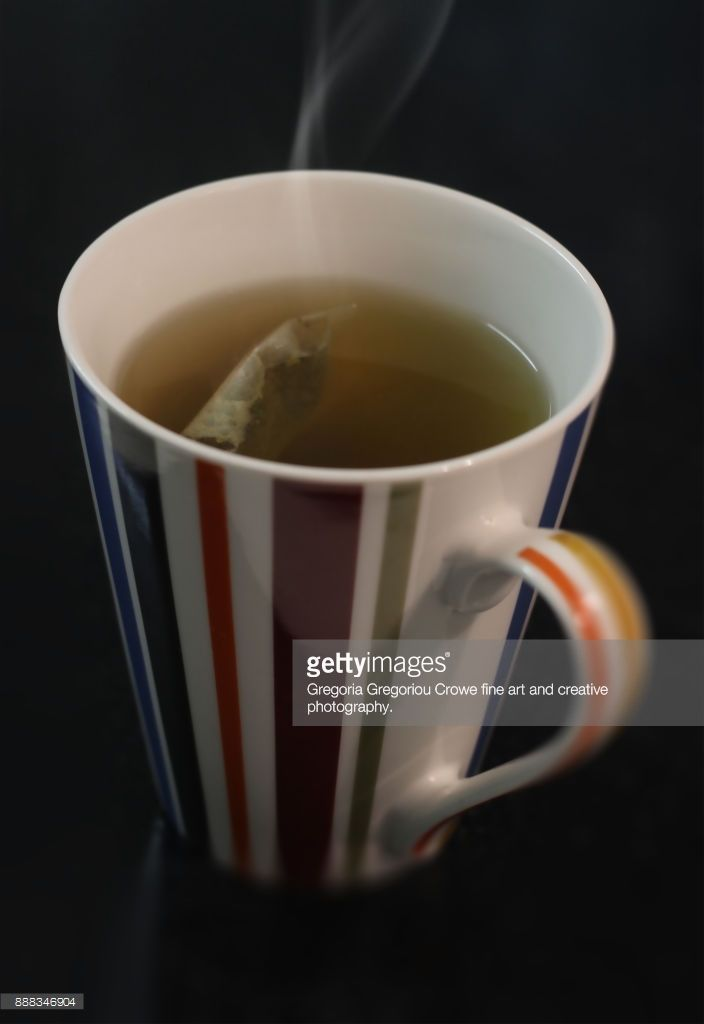 Close-up of steaming hot green tea in a striped mug on a black background.