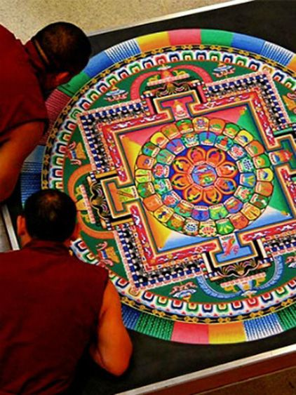 Monks finishing sand mandala, Tibet. Tibetan sand mandalas are carefully, lovingly created by hand and then destroyed to show the impermanence of all things.