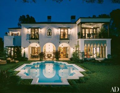 A coat of arms Auerbach saw in Cordova inspired the shape of the swimming pool. Landry and his associates Todd Riley and Marc Welch added Moorish details to the house, including wrought iron railings and arched windows. Mark David Levine landscaped the rear garden | archdigest.com