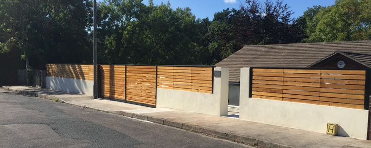 "Electric sliding gate and matching railings. Our modern design, the Kingston range. Constructed using Western Red Cedar. Powered using BFT Ares 1000 kit with full safety features. Sliding gate based on a ""track in ground"" set up."
