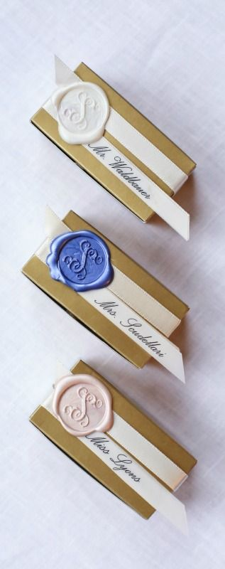 personalized place cards that double as wedding favors - gold candy boxes embossed with the bride and groom's married name and wedding date, tied with ivory ribbon, strips of parchment with each guest's name in script, and sealed with a monogrammed wax seal indicating meal choice!