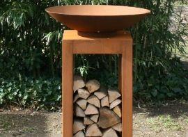 Cortenstalen vuurschaal geplaatst op een sokkel welke dienst doet als kleine opslag voor hout. ook te verkrijgen in staal