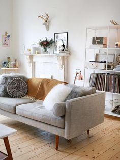 Like the mixture of honey coloured floorboards white walls and grey sofa