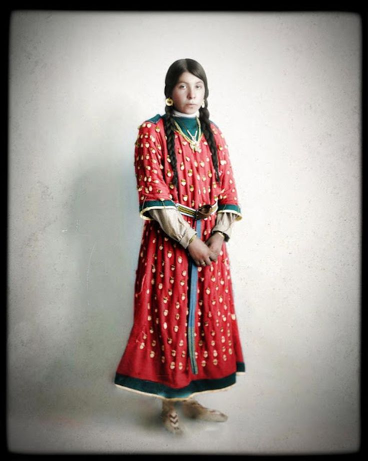 Rose Bompard Bird, of the Crow tribe, looks directly at the painter in a early 1900s red and green ankle-length dress.