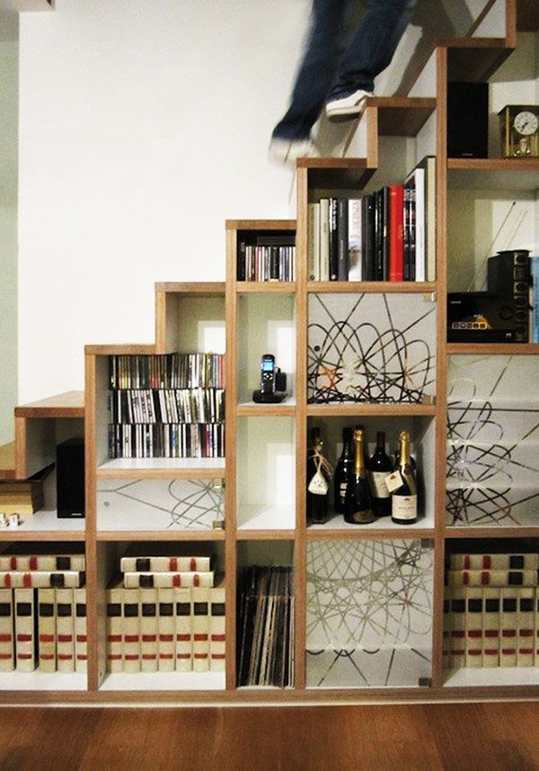 Diversely decorated shelves hidden away by the stairs (great for the NYC loft)