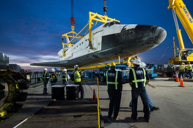 The Over Land Transporter (OLT) is moved into position below the space shuttle Endeavour not long after it was demated from the NASA 747 Shuttle Carrier Aircraft (SCA) during the early morning hours on Saturday, Sept. 22, 2012, at Los Angeles...