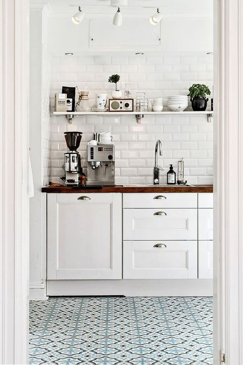 Blue printed tiles in white modern rustic kitchen, white cabinets, open shelving, butcher block counters and white subway tile