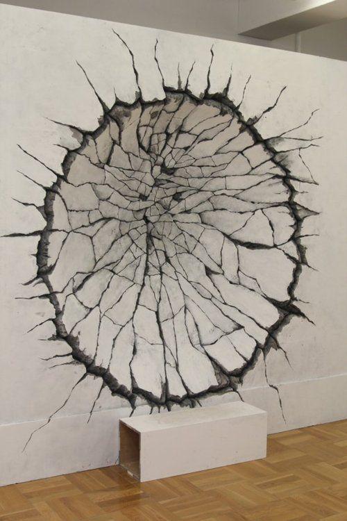 Art très réaliste. On dirait que ce trou a été formé par un tronc d'arbre que l'on aurait enfoncé dans le mur.