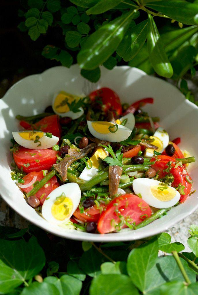 Салат Настоящий Нисуаз. Салат — 1 кочан Помидоры — 4 шт. Яйца вареные — 3 шт. Молодые луковицы — 3 шт. Сладкий красный перец — 0,5 шт. Зеленая стручковая фасоль — 200 г Чеснок — 1 зубчик Маслины мелкие — 2 ст.л. Анчоусы в масле — 8 филе Тунец в масле — 150 г Лимонный сок — 3 ст.л. для заправки Оливковое масло — 7 ст.л. Базилик зеленый — 8 листиков Винный уксус — 1,5 ст.л. Чеснок — 1 зубчик Морская соль Молотый черный перец