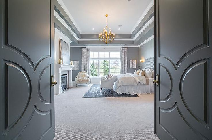 Gray double doors open to a gray bedroom featuring an overlapped tray ceiling accented with a brass tiered chandelier illuminating an accent wall clad in gray geometric wallpaper lined with a gray tufted headboard on bed dressed in platinum gray bedding and a white tulle bedskirt flanked by curved 3 drawer nightstands alongside a cream couch placed at the foot of the bed atop a black overdyed rug.