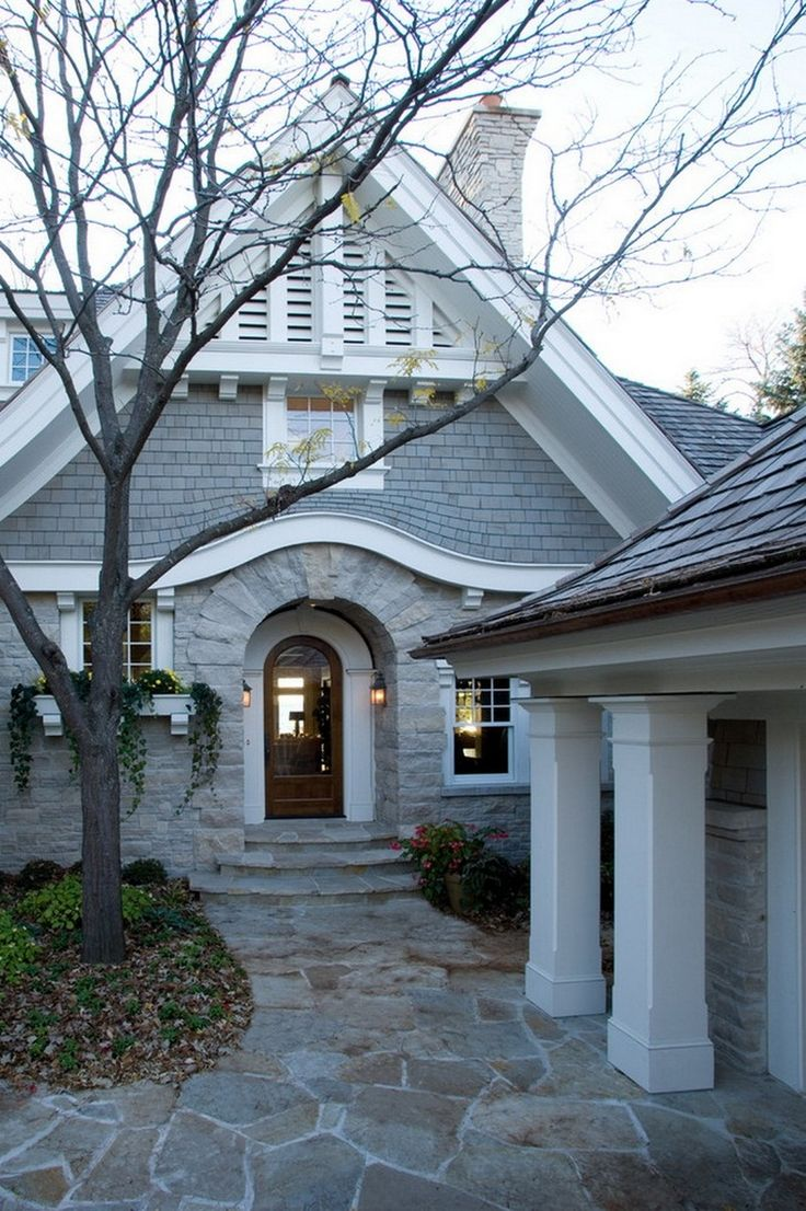 An Interesting Entry Way With Arched Wooden Door And Classic Style With Irregular Patterned Paving Pathway Classic cottage on the beautiful shores of Lake Home design