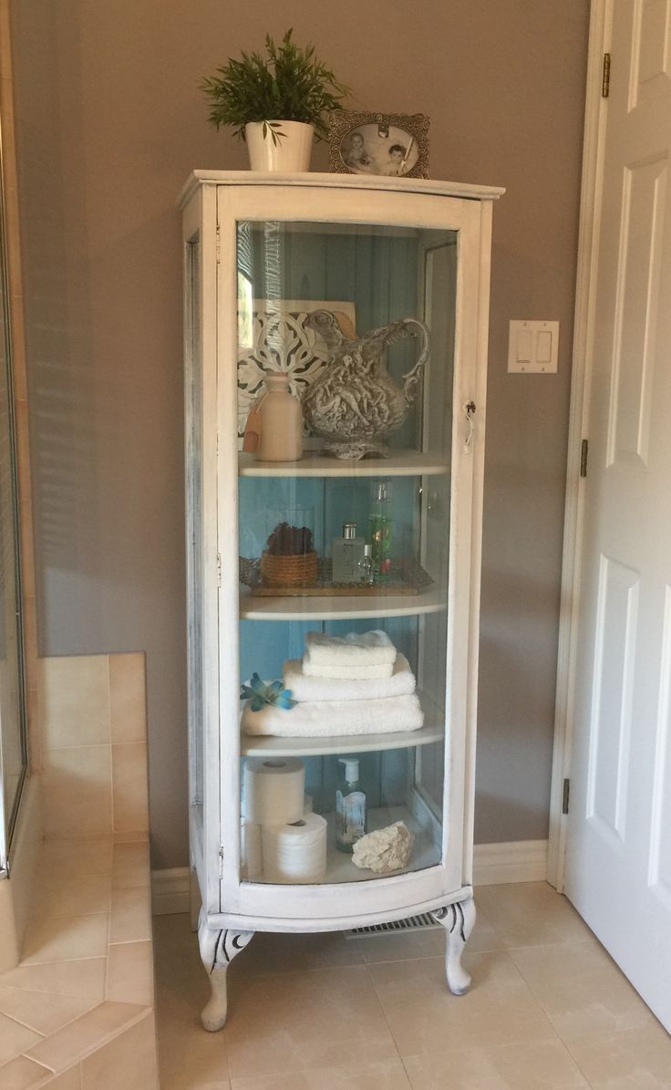 Shabby chic make over. Small curio cabinet painted with a DIY Chalk paint. Painted white with a turquoise backboard and lightly distressed.