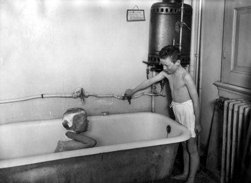 Badkamer. Twee jongens in een primitieve badkamer met ligbad en boiler.  Terwijl de ene jongen in bad zijn haar wast, draait de ander in onderbroek de kraan open. Op het bordje boven het bad: '1. Aansteekvlam aansteken. 2. Gaskraan aansteken. 3. Waterkraan openen. Nooit de waterkraan openen voor aansteekvlam brandt.'