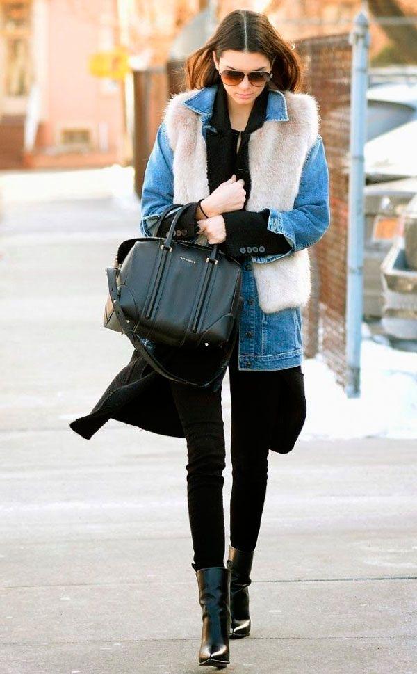 Street style look Kendall Jenner usando jaqueta jeansc, com colete de pêlo fake, calça preta e bota.