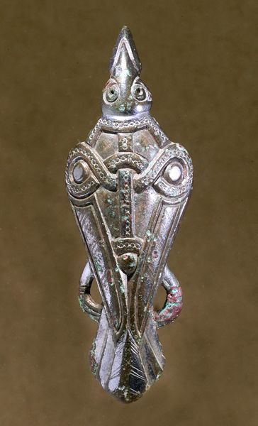 Bird-fibula. Bronze brooch gilded with silver showing a bird, maybe a raven. Dated to Late Scandinavian Iron Age (AD 400-1050). Uppåkra, Sweden. (Photography by Bengt Almgren, LUHM)