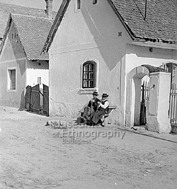 A felvétel vasárnap délelőtt készült, beszélgető öregek a padon - Páty, 1952