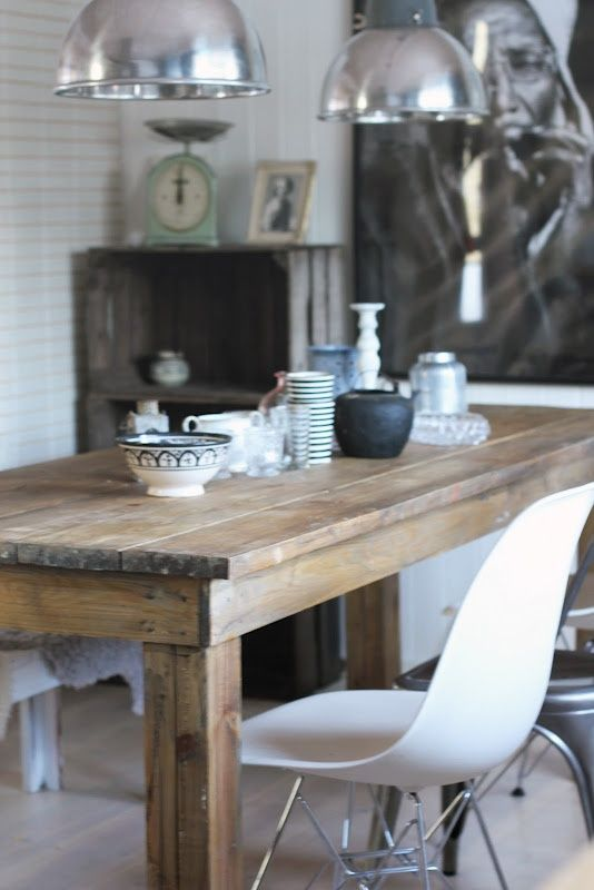 Set of two silver industrial lamps well placed over long timber dining table with mismatched dining chairs. Nice.