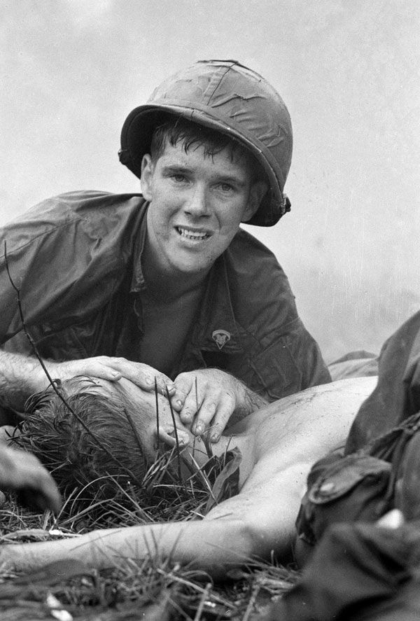 """Medic James E. Callahan of Pittsfield, Mass., looks up while trying to resuscitate a seriously wounded soldier north of Saigon in June 1967. AP Photo. Henri Huet."