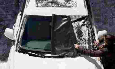 personne qui retire une bâche du pare-brise de sa voiture