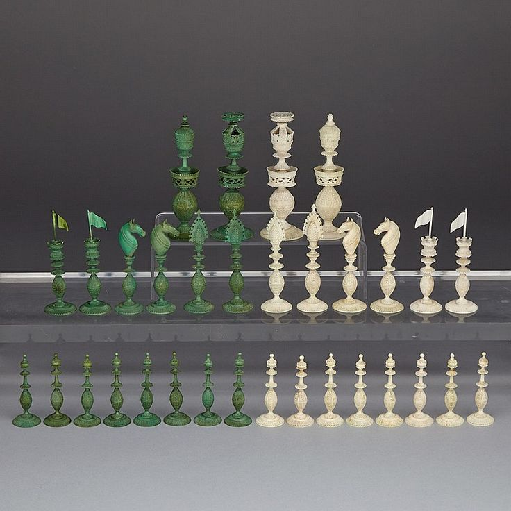 """ANGLO-INDIAN TURNED AND CARVED IVORY CHESS SET, KASHMIR, EARLY 19TH CENTURY one side stained green, each piece finely carved all over with foliate decoration, the kings and queen pierce carved with turreted waists, bishops with pierced miters, knights with horse heads, rooks as turrets with flags, height 4.75"""" - 12.1 cm"""