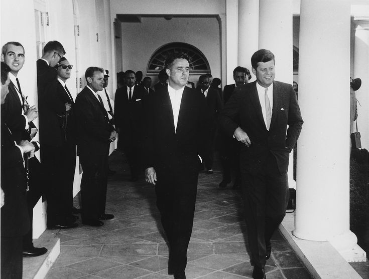 28 Aug 1961. Sargent Shriver, director of the Peace Corps,(center) and U.S. President John F. Kennedy (right) at the White House.