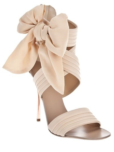 Beige fabric high heeled sandals from Giuseppe Zanotti Design featuring pleated fabric straps and a large bow detail to the side. The sandals have a suede panel to the back with a zip fastening.