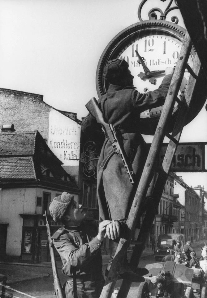Soviet troops seen setting the Martin Halisch clockmaker's store clock on Market Square in Breslau in 1945. Note the bullet hole through the clock face.