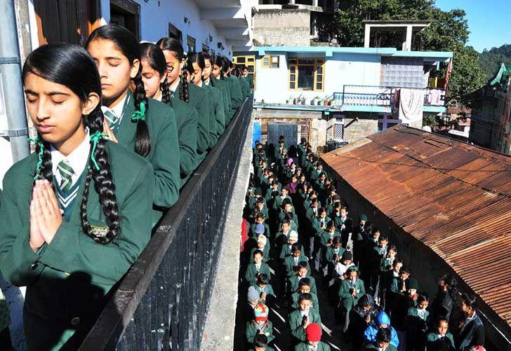 Escolares indios rezan durante la asamblea de la mañana en su escuela en Shimla el 17 de diciembre de 2014. Le estaban rindiendo homenaje a los escolares y personal de escuela paquistaníes muertos después de un ataque a una escuela militar en la conflictiva ciudad de Peshawar