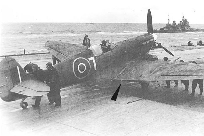 A Supermarine Seafire is readied for take off later in the war. Even though Seafires were modified for carrier operations, they still lacked take off flaps (until the Seafire 47). The Royal Navy opted to keep the simple wooden block system employed by Spitfires in the club runs to Malta. The blocks that keep the flaps down for take off can just be seen in this photograph. There are two per side as Spitfire flaps are split into two sections. Photo: Royal Navy