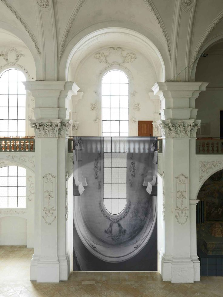 Abbey Church of Bellelay, built by Franz Beer in 1714, is made of grandiose ornamented pillars and arches, huge spaces of contemplation and art in the natural light. While navigating in its atmosph...