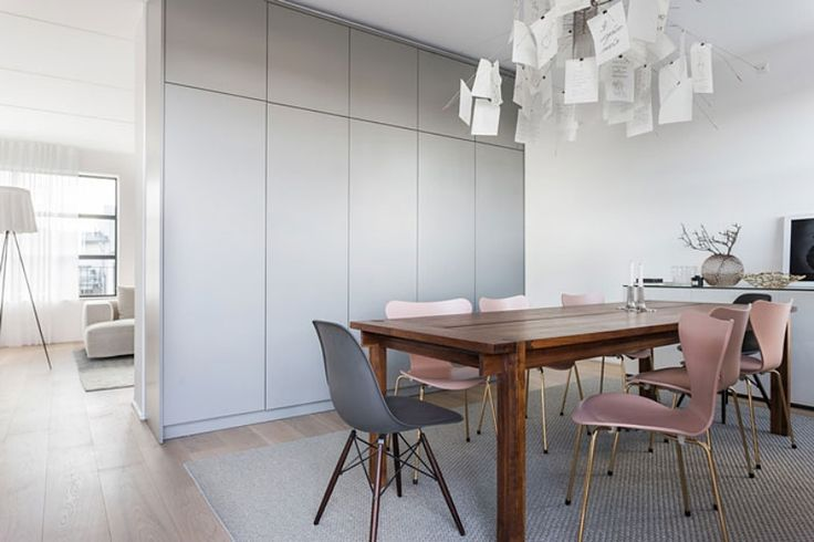 Dining room with built-in storage, a large wooden table, six anniversary edition Sjuan chairs in pink and brass by Arne Jacobsen for Fritz Hansen, two grey Eames DSW chairs and ceiling lamp by Ingo Maurer. | HEM&RUM.se | #oscarproperties #diningroom