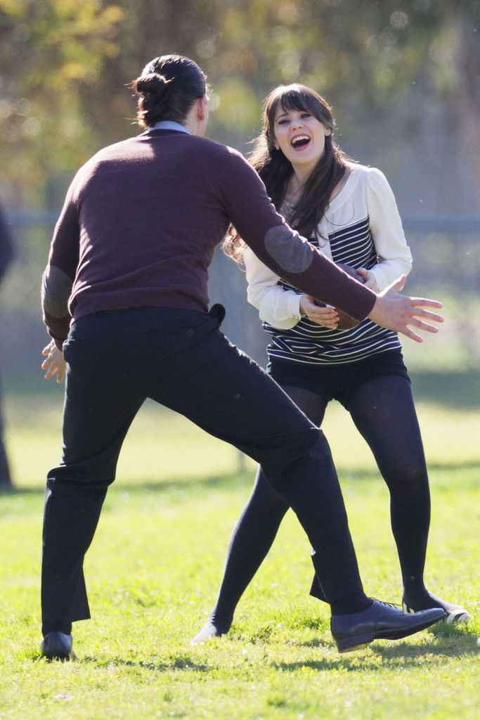 Zooey Deschanel Photos Photos - Zooey Deschanel and Steve Howey play some football at a Los Angeles park for a 'New Girl' scene. - Zooey Deschanel and Steve Howey on Set