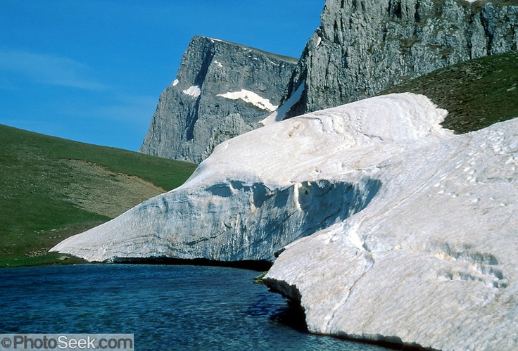 Dragon Lake, snow banks, Gamila Peak, Vikos-Aoos National Park, north Pindus Mountains (Pindos or Pindhos), Zagoria, Epirus/Epiros, Greece, Europe. The northeast wall of Vikos Gorge is Mount Tymfi (or Greek: , also transliterated Mt Timfi, Tymphe, or Tymphi), near the 40 degree parallel. Tymfi forms a massif with its highest peak, Gamila, at 2497m (8192 feet), the 6th highest in Greece. Zagori is a region and a municipality in the Pindus mountains in Epirus, in northwestern Greece.
