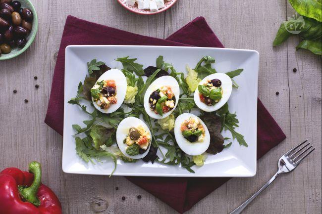 Le uova alla greca sono un saporito e coloratissimo antipasto, composto da uova bollite farcite con feta, peperoni, olive e acciughe.