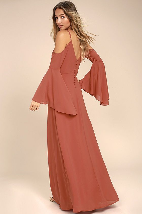 """Every fabulous mademoiselle will be saying """"bonjour"""" to the Glamorous Greeting Rusty Rose Maxi Dress! Lovely Georgette fabric swings from adjustable spaghetti straps into long, cold shoulder bell sleeves. Princess-seamed bodice (with back button placket) meets a fitted waist, and maxi skirt."""