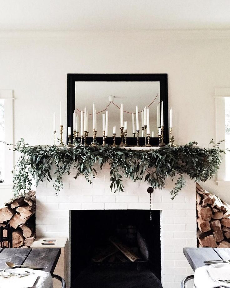 Simple and organic, minimalist black and white interior with stacks of firewood, a vignette of vintage brass candlesticks with white tapers, and a freehanging eucalyptus garland. Gorgeous!