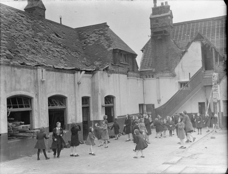 Children play in the playground of Moorside Road School in South East London. The school has been badly damaged by an air raid, with windows missing, tiles missing from the roof and planks of wood being stored inside the windowless shell of the building. -