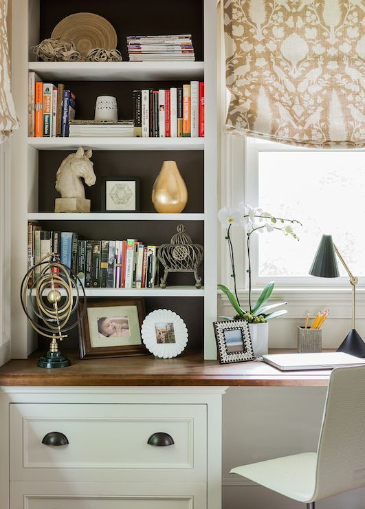 Gorgeous home office features built in desk situated under window dressed in Schumacher Chenonceau Fabric flanked by countertop bookcases with backs of shelves painted chocolate brown.