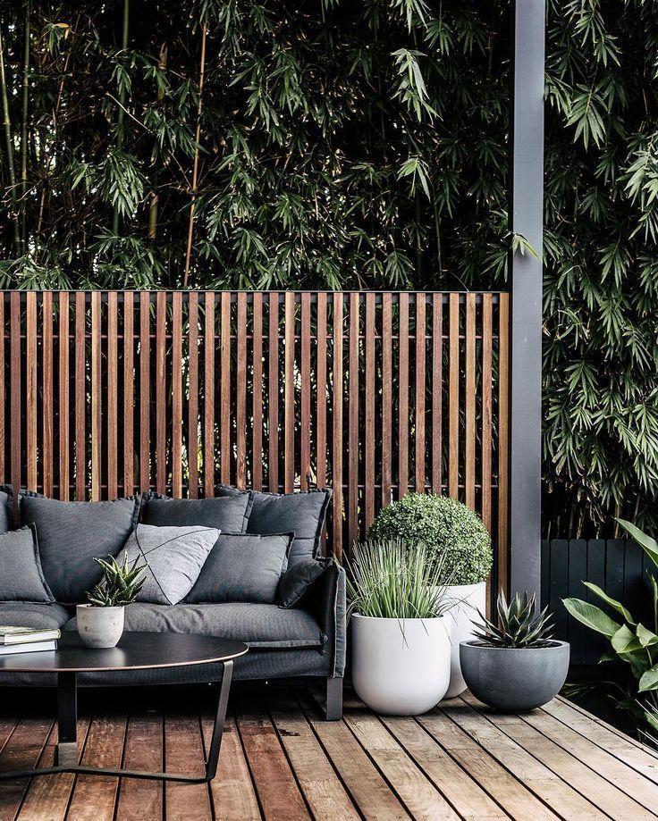 Outdoor Sofa und Topfpflanzen gegen diesen Zaun.