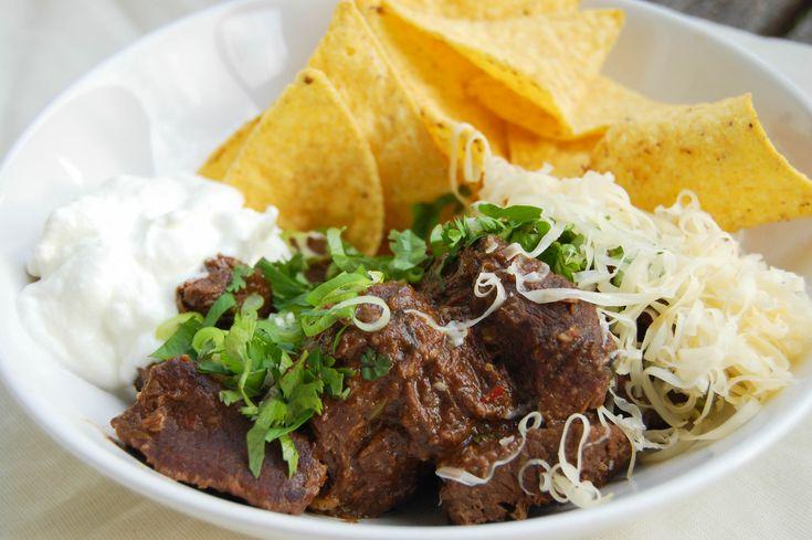 Chili con carne naar tex-mex recept. Runderstoofvlees met verschillende soorten chili's. Geserveerd met nacho's, sour cream, bosui, koriander en kaas.