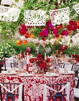Flying Colors    The trees are festooned with garlands of papel picado (traditional Mexican cut-paper streamers), silk and tissue-paper flowers, paper stars and lanterns. Candlesticks with tall taper candles help balance the busy table dressings.    Tables, chairs, china, crystal, flatware and napkins, all from La Posada de Santa Fe Resort & Spa.