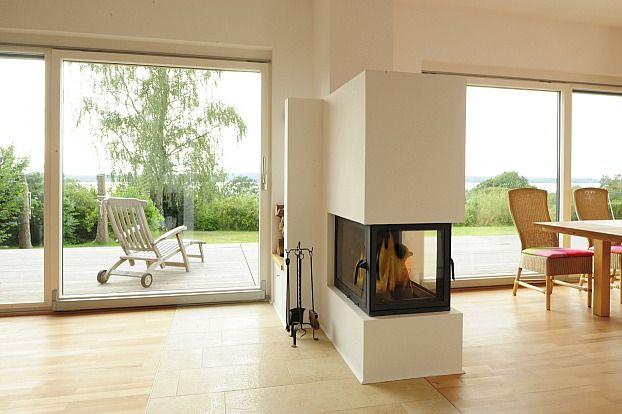 Der Kamin als Raumteiler! Dieser Kamin macht sich als Raumteiler zwischen den Funktionszonen Wohnen und Essen verdient und hat auf beiden Seiten ein großes Sichtfenster. Schöne Stunden vor dem Feuer lassen sich auf dem Sofa genauso genießen wie am Tisch. Baufritz