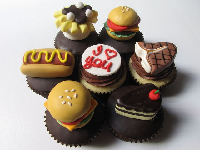 """Foodie Cupcakes!  Vanilla cupcakes filled with chocolate ganache, covered in chocolate fondant, and topped with handcrafted fondant cheeseburgers, poutines, hot dogs, steaks, and slices of cake.  The cupcakes were ordered by someone in Australia for her boyfriend in Montreal hence the """"I ♥ You"""" which I tried to make look like it was written in ketchup."""