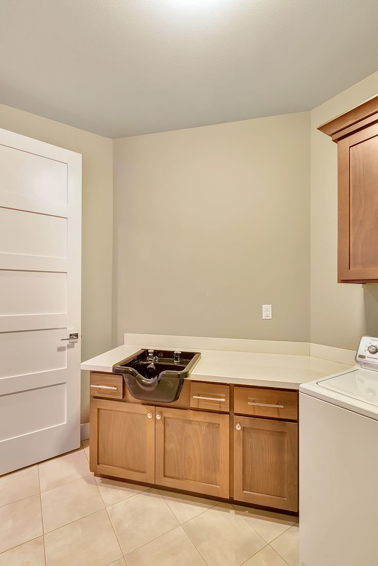This laundry room features a salon sink for at home hair color and rinse!