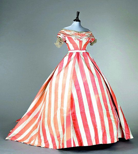 A pink and white striped moiré ball gown, circa 1865, the short bodice trimmed with white bugle beads and lace, over elongated, oval shaped skirt
