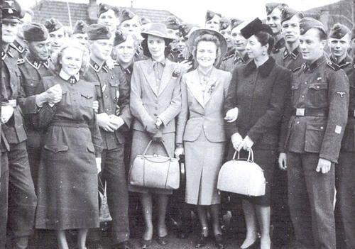 Singer Aino Palomäki, pianist Alice Pacius, violinist Pippa Haikala and Mrs. Marjatta Martola visit with men of the SS Finnisches Freiwilligen SS Battalion der Waffen SS along with Lotta Svärd volunteers in April 1942.