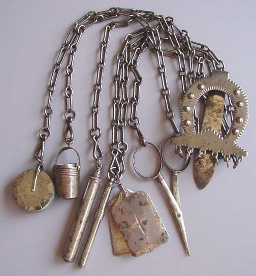 """Circa 1820. Sewing Chatelaine  3-1/2"""" belt clip chatelaine of steel and 12-facet cut steel brads holding 11"""" chains with a 1-1/2"""" thimble and bucket holder, 1-1/2"""" wheel type pin cushion, 2-1/8"""" aide memoir with 2 thick bone pages, 3-1/3"""" scissors, 2-3/4"""" tube holding a bone handled 2"""" punch and 2-5/8"""" retractable pencil with thick lead."""