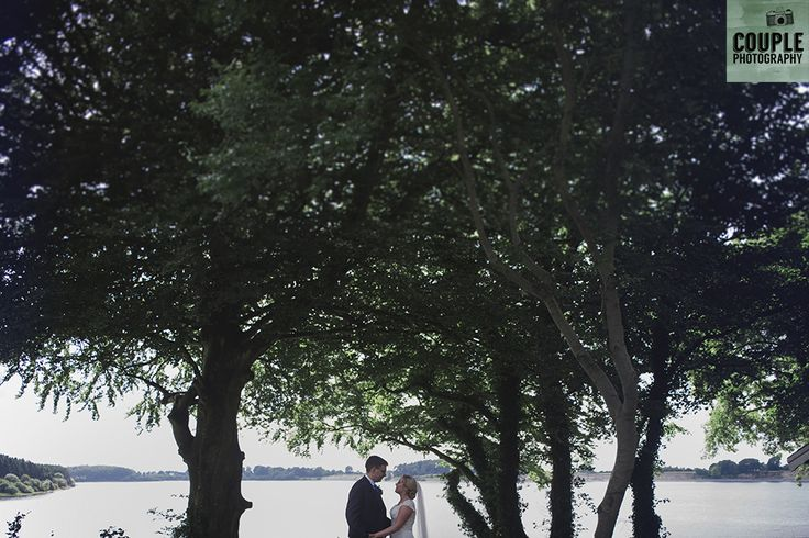 The bride & groom in front of the beautiful Blessington Lake. Weddings at Tulfarris Hotel & Golf Resort photographed by Couple Photography.