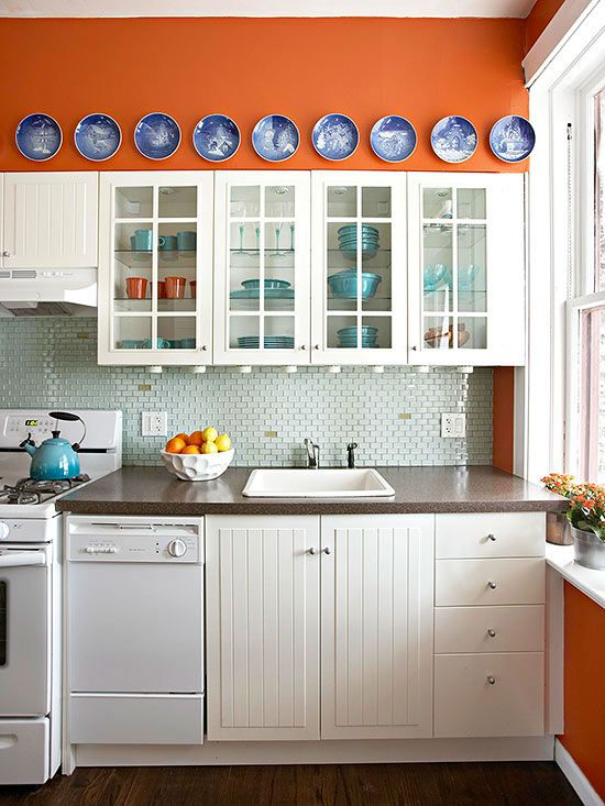 Fuse complementary shades -- colors across from each other on the color wheel -- to create high-contrast designs that demand attention. This kitchen mixes burnt orange with cool blue accents to create a space that wraps visitors in a warm embrace. Navy blues pop against the vibrant orange walls, which highlight white finishes. Robin's-egg dishware and a barely-blue backsplash balance the warmer hues while providing a tantalizing transition between the zesty walls and crisp white cabinets.